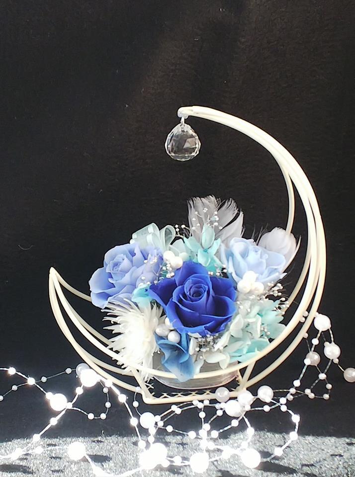 ブルーのバラを使用した プリザーブドフラワーアレンジ 人気の月型の花器に 幸運を呼ぶサンキャッチャーを