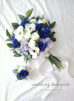 上品なホワイトとブルーのクラッチブーケ。 トレンドのアネモネとサムシングブルーとしてブルーのバラをメインに仕立てております。 アーティフィシャルフラワーを使用しており、挙式後も長く楽しんでいただけます。